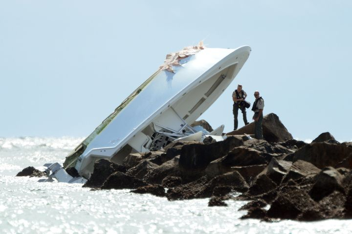 Investigators look over the overturned boat in which Miami Marlins pitcher Jose Fernandez was killed, Sunday, Sept. 25, 2016,