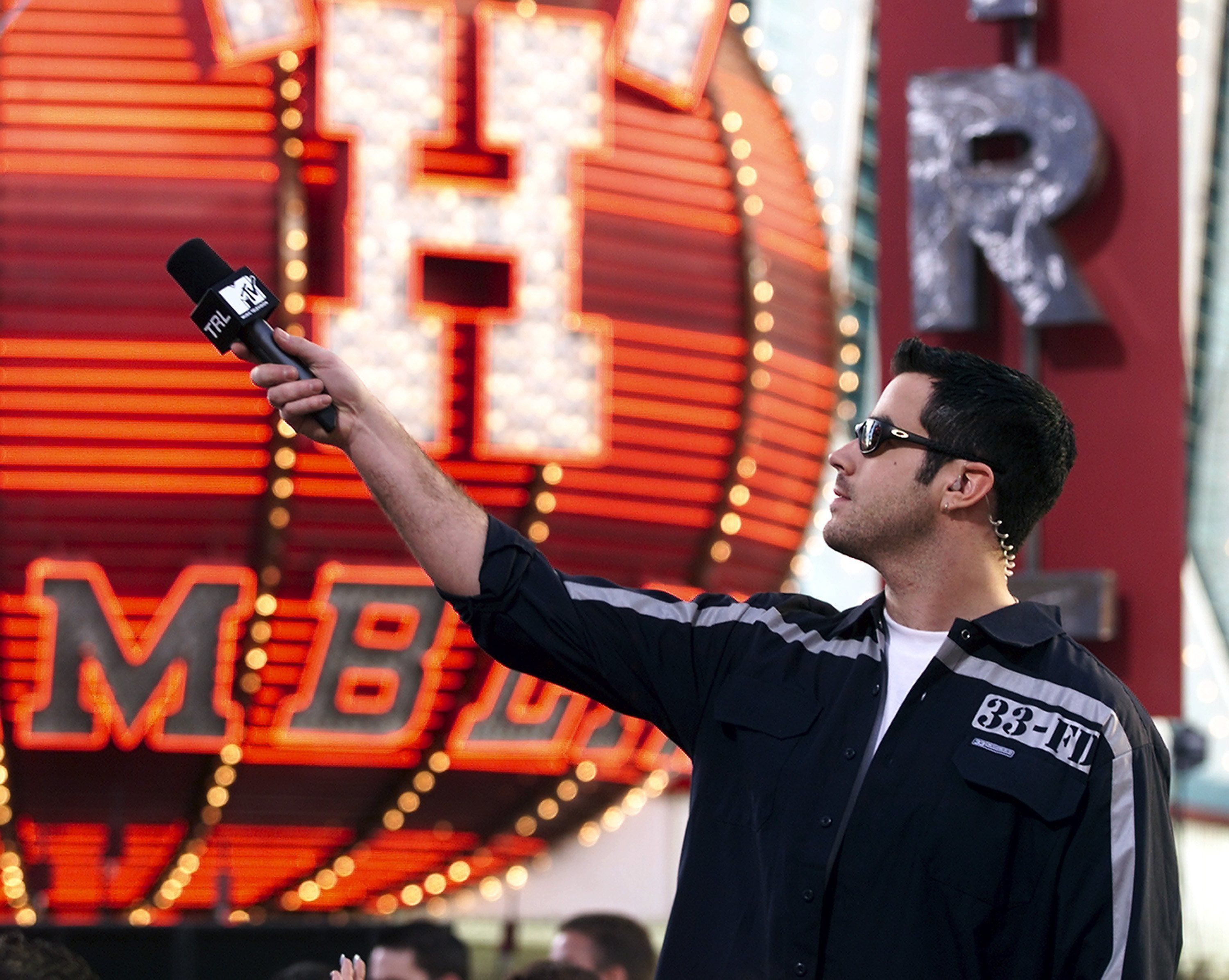Host Carson Daly holds a microphone out while taping segments for MTV's 'Total Request Live' Spring Break show at the Fremont Street Experience March 11, 2000 in Las Vegas, Nevada.  (Photo by Ethan Miller/Getty Images)