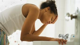 African woman leaning over bathroom sink with head in hand