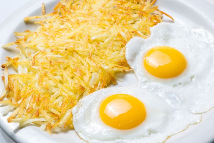 Hash browns sitting next to two eggs on a plate.