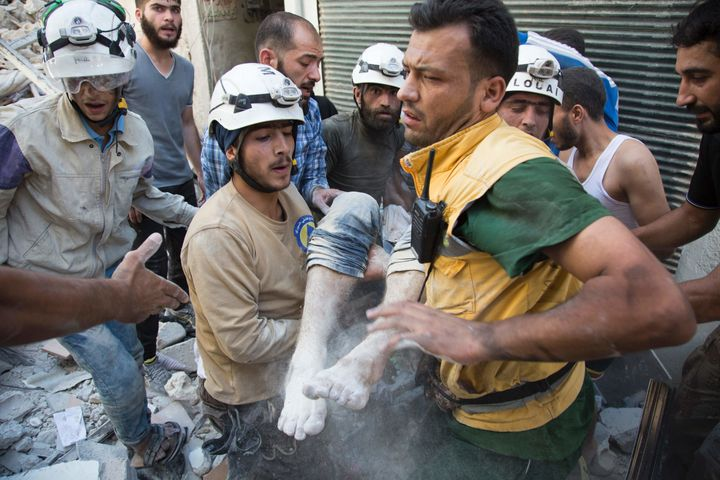 Syrian civil defense volunteers, known as the White Helmets, carry a body after digging it out from under the rubble of a bui