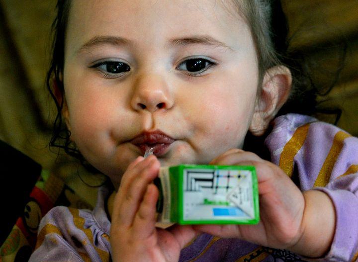 WOONSOCKET, RI - MARCH 01: One-year-old Jaeliece Ortiz enjoys some of the food (fruit juice) her mother (Rebecka Ortiz) just