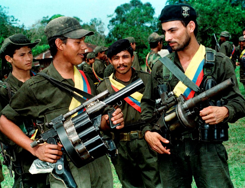 FARC fighters pose with their weapons after a patrol in the jungle near the town of Miraflores. Aug. 7, 1998.