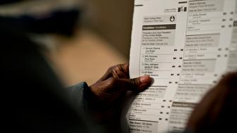 A voter holds a ballot while waiting to vote at a polling station in Chicago, Illinois, U.S., on Tuesday, Nov. 6, 2012. U.S. President Obama is seeking to overcome the drag of high unemployment and economic weakness that has frustrated predecessors' re-election bids, while his Republican rival Mitt Romney reaches for an upset to propel him beyond his party's standing and swamp an electoral map stacked against him on the final day of the presidential race.  Photographer: Daniel Acker/Bloomberg via Getty Images