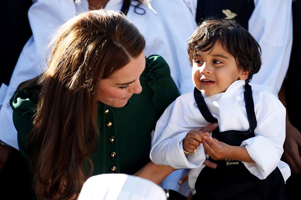 The Duchess of Cambridge, picks up a child while posing with a group of children during the Taste of British Columbia ev