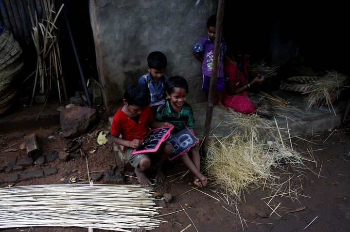 Slum living children are seen as they are practicing alphabet letter at a slum on the eve of World Literacy Day in the easter