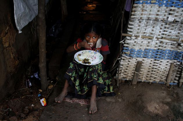 A below poverty line family girl eats food as she sits outside of her parents living makeshift at a slum...