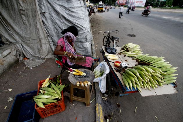 A slum living girl hides herself to avoid camera as she prepares roosted corns on way side before to...