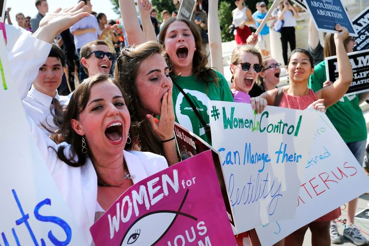 Anti-abortion demonstrators cheer as the ruling for Hobby Lobby was announced outside the U.S. Supreme Court in Washington Ju