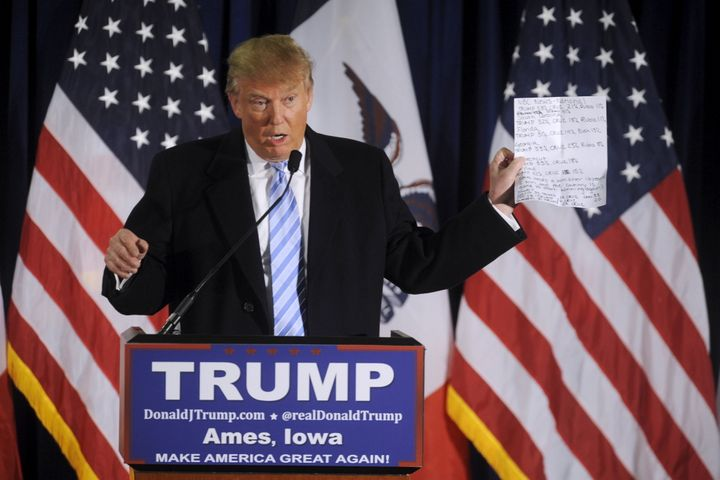 Republican presidential nominee Donald Trump holds up a sheet with poll numbers as he speaks at a rally in Ames, Io