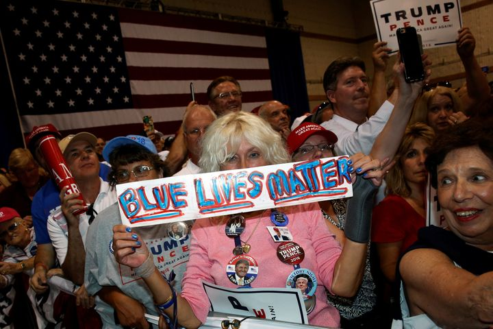 """A woman holds a sign reading """"Blue Lives Matter"""" as Republican presidential nominee Donald Trump holds a rally with supporter"""