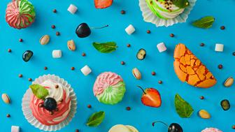 Geometrically arranged variety of sweets (macarons, berries, cupcakes, marshmallows) on a vibrant blue background. View from above.