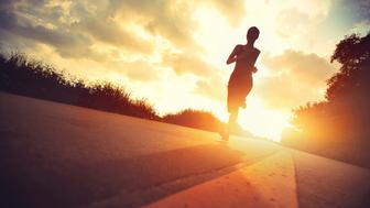 Runner athlete running at seaside road. woman fitness silhouette sunrise jogging workout wellness concept.vintage effect