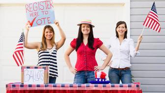 Young women set up a voter registration table outside their garage. Props include the American flag, a ballot box, and a handmade sign reading 'register to vote here.' Colors red, white and blue represent the United States of America.