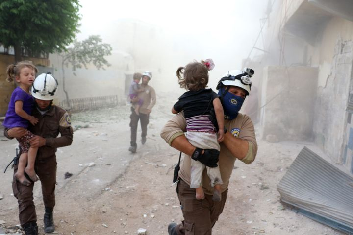 Search and rescue team members carry wounded kids after an airstrike hit residential areas in Aleppo, Syria on May 31, 2016.