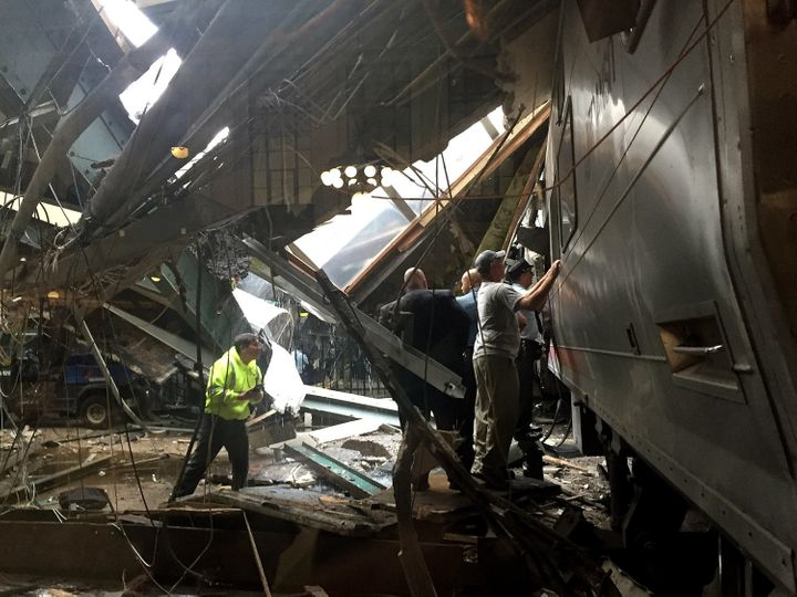 Train personnel survey the New Jersey Transit train that crashed into the platform at the Hoboken Terminal on Thursday mornin