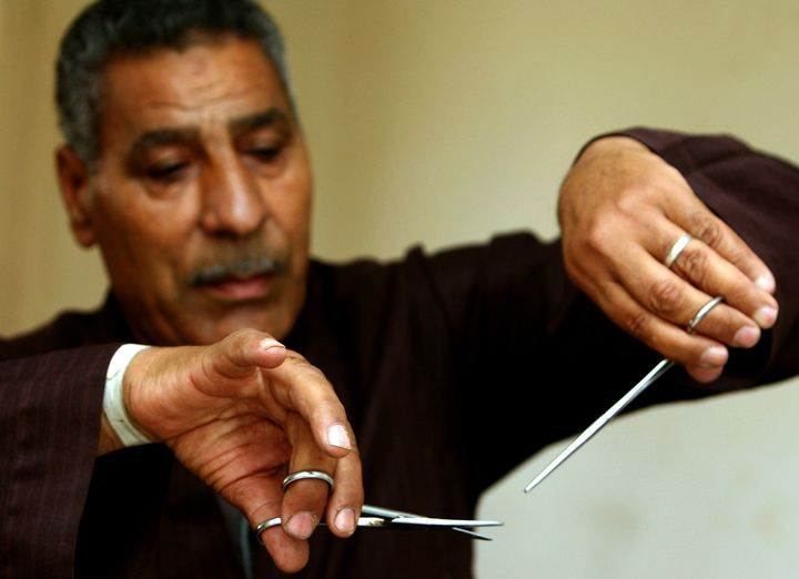 Hassan Hafez, a barber, mimics the way he used to perform female genital mutilation (FGM) in Egypt,June 13, 2006. Becau