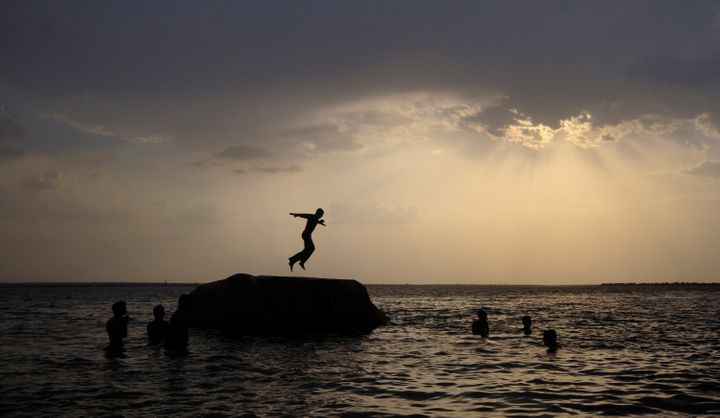 A boy prepares to jump off a rock into the waters of the Osman Sagar Lake near the southern Indian city of Hyderabad May 29, 2011.