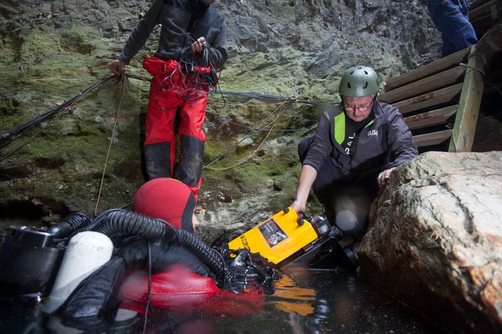 The team of explorers prepare to send the remotely operated vehicle to the cave's bottom.