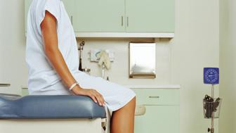 Young woman on table in doctor's office, mid section