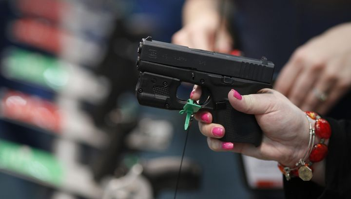 An attendee handles a firearm on the exhibit floor during the National Rifle Association annual meeting in Louisville, Kentuc