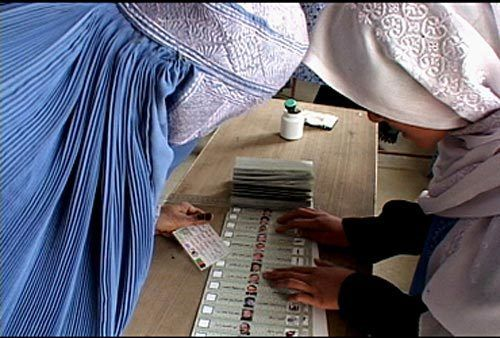 <p>Oct. 9, 2004 — A Joint Electoral Management Body employee, right, explains how to fill out an election ballot to an Afghan woman in the village of Raban during Afghanistan&#39;s first democratic presidential election October 9th.</p>