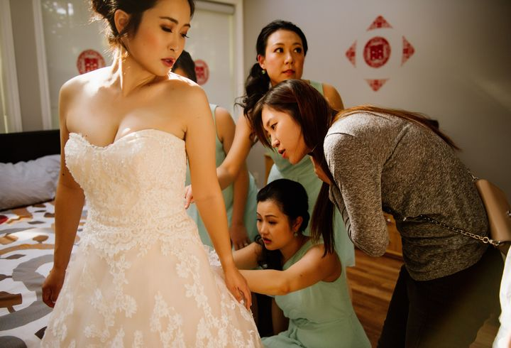 Jo Du and the women in her wedding party work to try to fix Du's wedding gown.