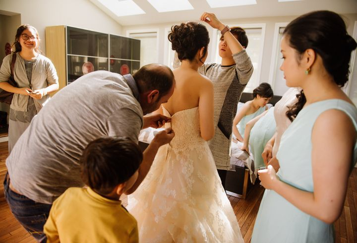 Dudu works at repairing the bride's zipper.