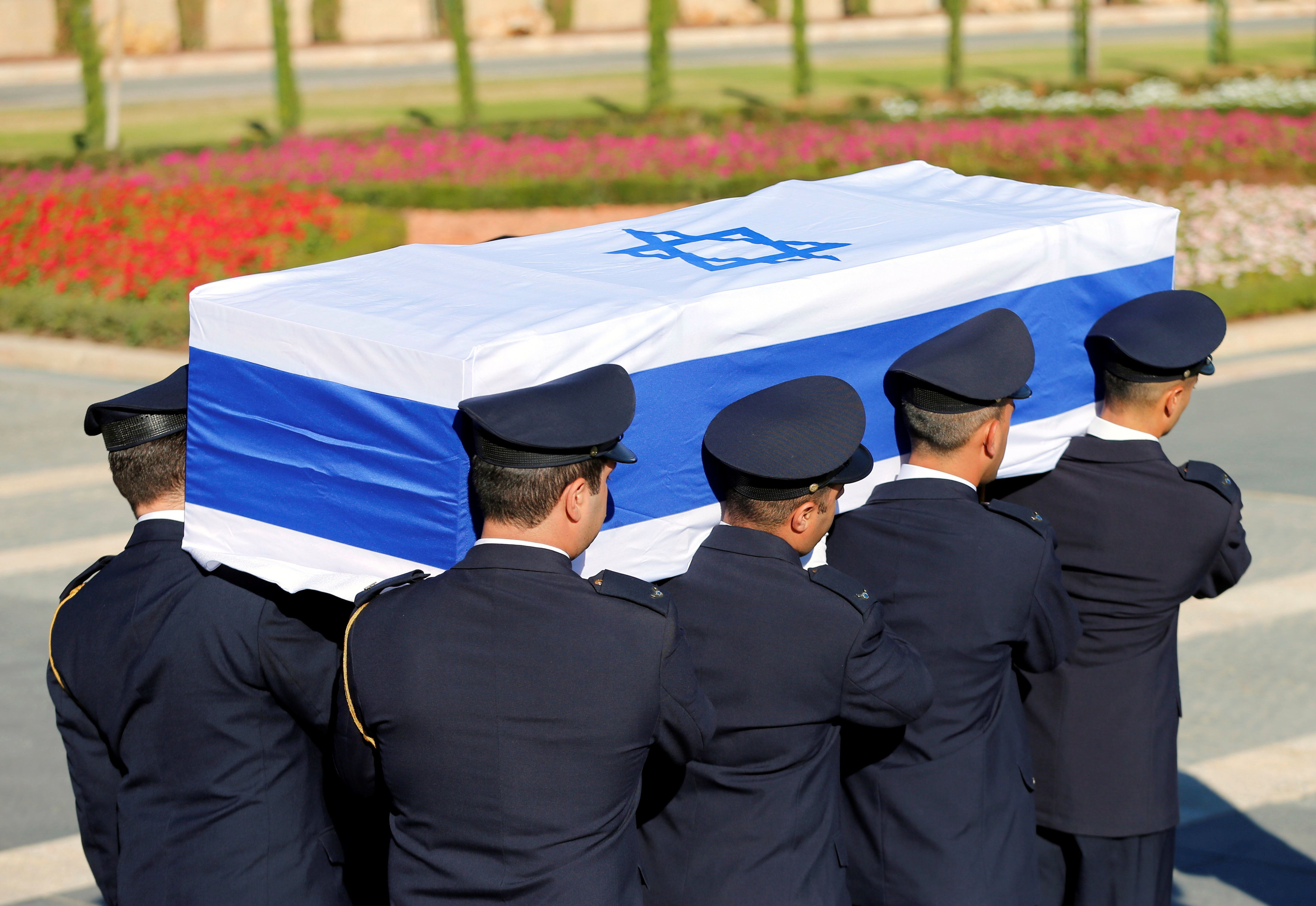 Members of the Knesset guard carry the flag-draped coffin of former Israeli President