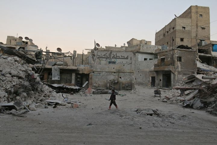 A boy walks amid damaged buildings in the rebel held area of al-Kalaseh neighbourhood of Aleppo, Syria, on Thursday.