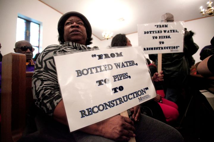 A woman holds a sign during a prayer service before a rally for clean water in Flint, Michigan, in February. Flintwater