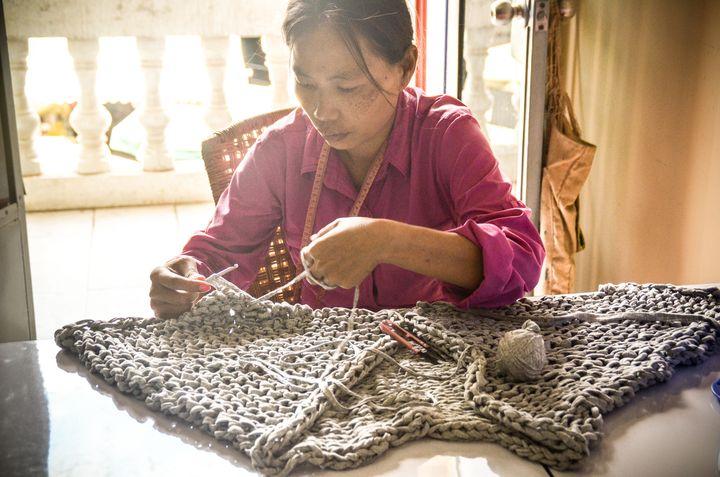 Tonlé employee Ming Eng hand-knits fabric yarn into a cardigan.