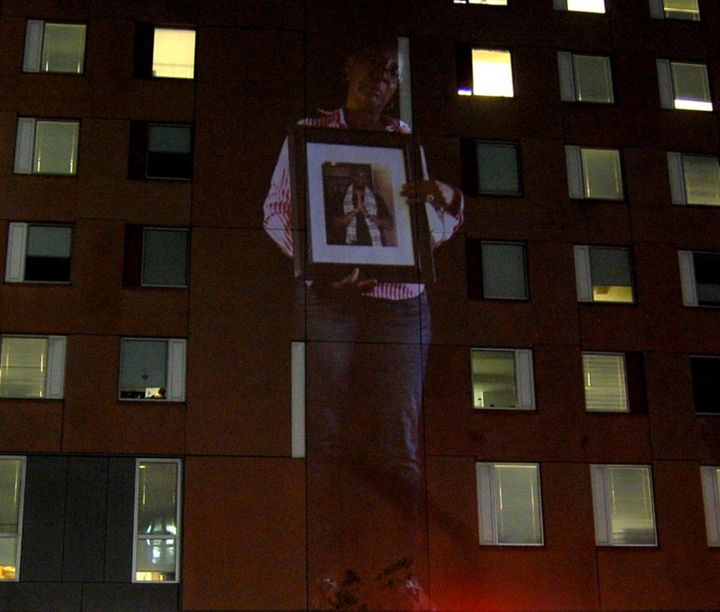 A projection of a mother holding a picture of her slain son on the Boston Police Department building.
