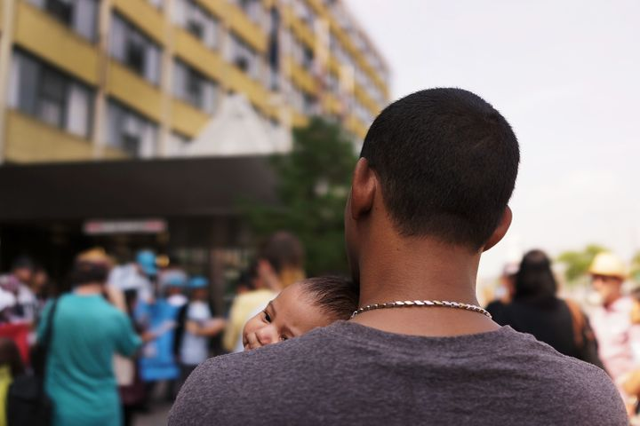A man and child, who are both homeless, participate in a rally in support of residents at the controversial Pan Am Shelter in