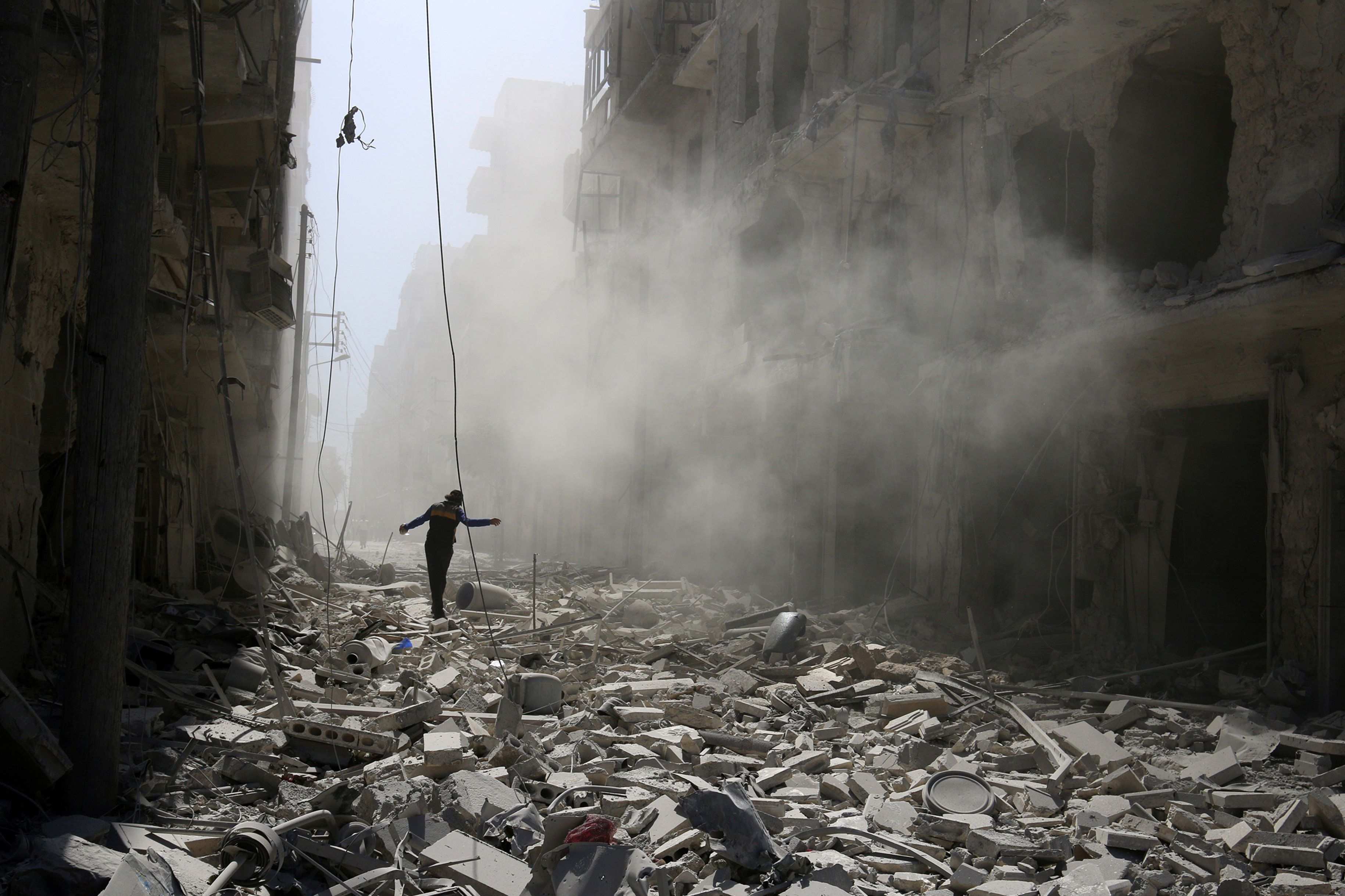 A man walks on the rubble of damaged buildings after an airstrike on the rebel held al-Qaterji neighbourhood of Aleppo, Syria September 25, 2016. REUTERS/Abdalrhman Ismail      TPX IMAGES OF THE DAY