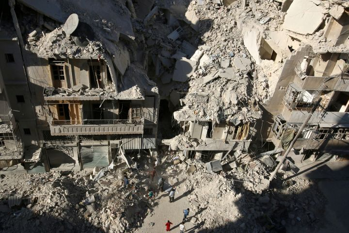 People dig in the rubble in an ongoing search for survivors at a site hit previously by an airstrike in the rebel-held Tariq