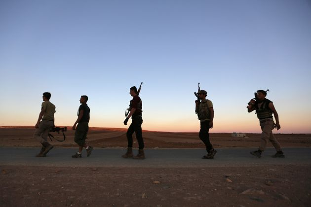 Rebel fighters carry their weapons in northern Aleppo countryside, Syria September 30,