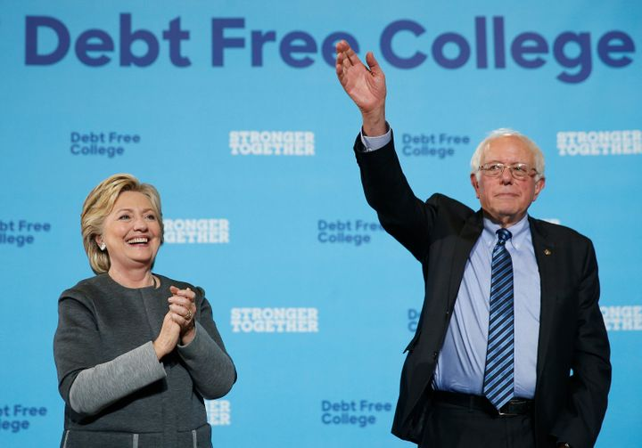 Hillary Clinton, left, and Bernie Sanders wave to the crowd at the conclusion of a campaign event at the University of New Ha