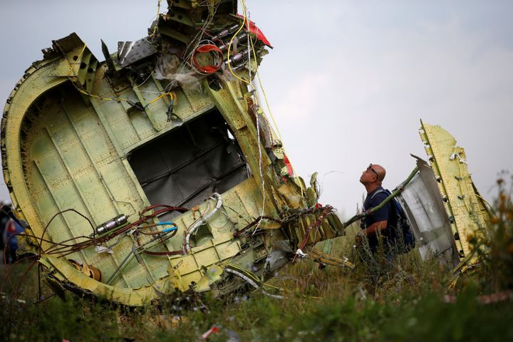 A Malaysian air crash investigator inspects the crash site of Malaysia Airlines Flight MH17, near the village of Hrabove (Gra