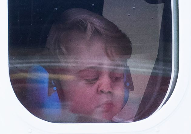 Prince George peers out of his sea plane's window as his family departs Victoria, Canada, on