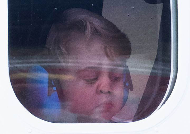 Prince George peers out of his sea plane's window as his family departs Victoria, Canada, on Saturday.