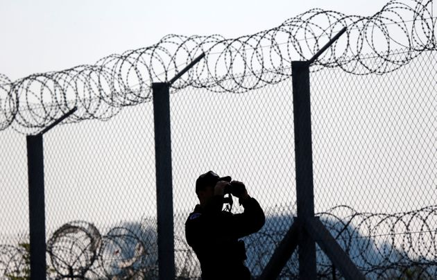 A Polish policeman patrols at the Hungary and Serbia border fence near the village of Asotthalom, Hungary,...