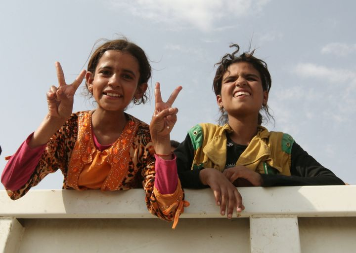 Displaced Iraqi girls from the northern Iraqi town of Qayyarah sit in a vehicle belonging to Iraqi security forces as th