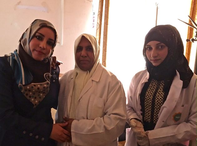 Iraqi women, some of them nurses, pose for a photograph at a medical center in