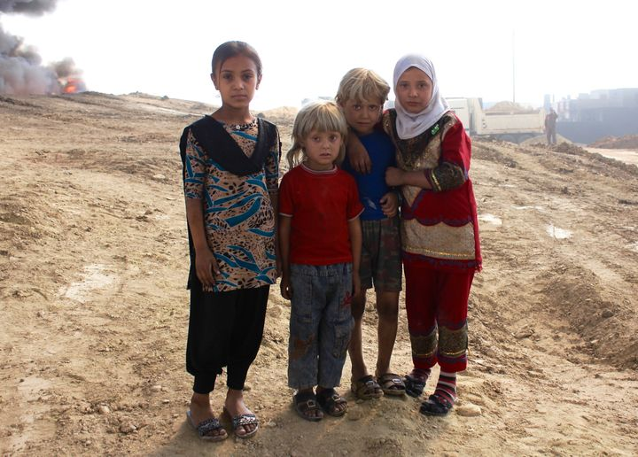 Children stand near a burning oil well, lit ablaze by ISIS in their retreat, just over a month after Iraqi forces drove out t