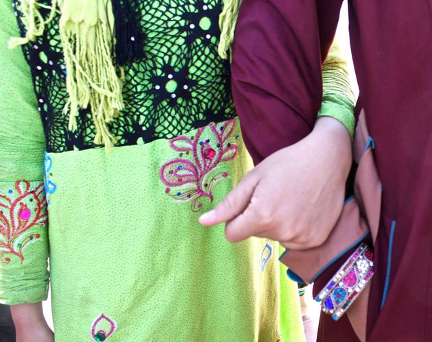 Teenage Iraqi girls stand, arm in arm, wearing brightly colored, intricately adorned clothing banned...