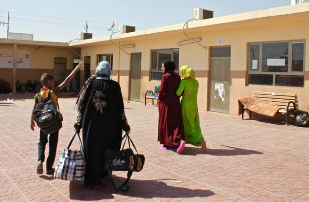Internally displaced Iraqis from former ISIS-held areas walk through Debaga camp in Iraqi