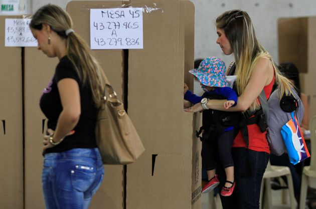 A woman carrying her daughter casts her vote in a referendum on a peace deal between the government and...