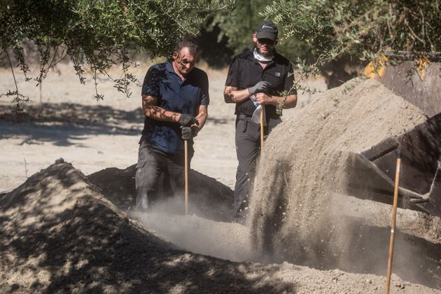 South Yorkshire Police watch on as a bulldozer excavates soil from under olive trees at the search site...