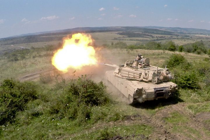 An Army Abrams tank hurls a 48-pound armor-piercing projectile in training for high-intensity warfare.